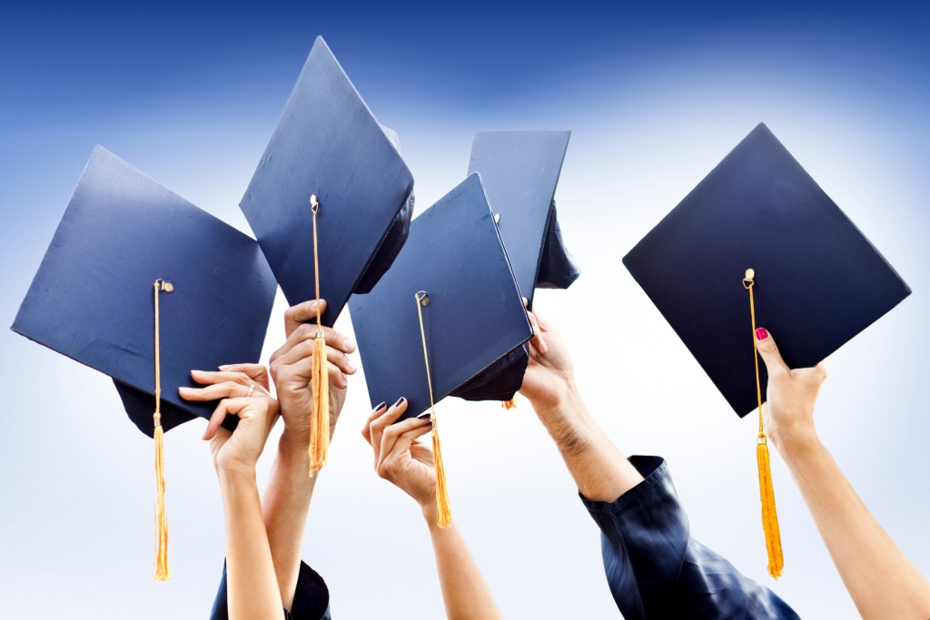 Group of people throwing graduation hats in the air